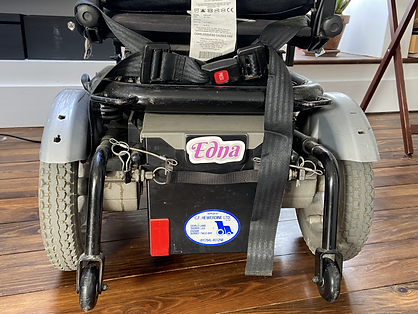 The bottom of Kyla's power chair from behind, in between large grey wheels is a bumper sticker that says 'Edna' in a camp pink font.