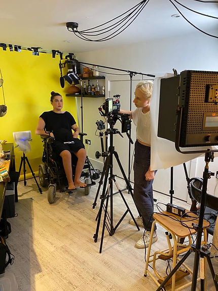 On a cluttered set in the kitchen, Kyla is serious as she sits in a power chair in front of a yellow backdrop gaffer taped to the ceiling. A microphone on a boom above her head. Intent and focused, Lou stands behind the camera facing Kyla, they are looking at a monitor attached to the camera. They are surrounded by cables, lights and stands.