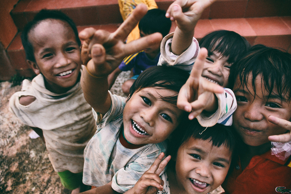 Children posing for camera with smiles and hand gestures indicating peace.