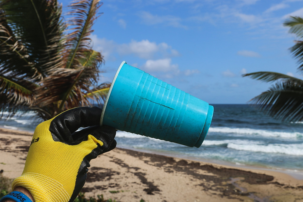 blue plastic cup on beach being picked by person wearing yellow gloves
