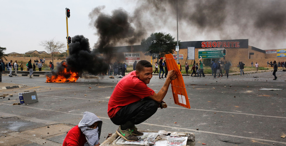 A protestor shelters behind a piece of metal while he is fired at by police during a violent protest in Eldorado Park, Johannesburg, South Africa, 08 May 2017. Reports state that the local community took to the streets blocking major roads including the N1 and N12 as they protested over a lack of housing and land for their community.