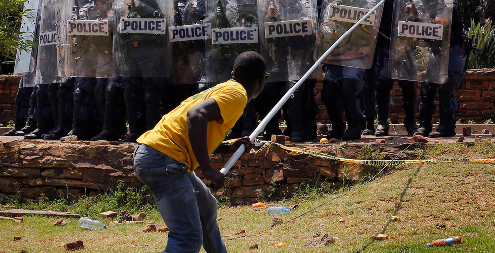 A protester faces off with anti riot police at the Union Buildings, during another day of demonstrations against fee increases at universities, in Pretoria, South Africa, 23 October 2015. The students have been demonstrating for nine days against a proposed fee increase and has spread to other major universities in the country.