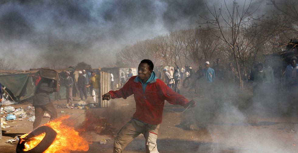 A protestor attacks police officers during running battles in a shanty town attached to Soweto after the police through a court order had attempted to evict them from land they illegally  occupied, Johannesburg, South Africa, 03 September 2007