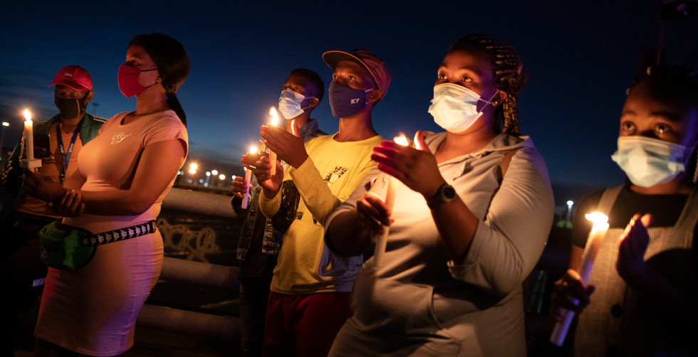 Members of the public stand with candles during a memorial for victims of the Covid-19 Corona virus on New Year's eve who have died in the city during 2020, Johannesburg, South Africa, 31 December 2020. The vigil was organized by the city of Johannesburg.  Level 3 lockdown was implemented last week due to second wave of infections sweeping across the country many of which are  cases of a new variant of the Corivd-19 Corona virus 501.v2, a mutated SARS-CoV-2 variant which holds a higher transmission rate. South Africa is the first African nation to pass 1 million infections.