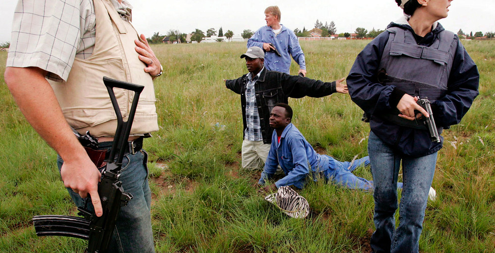 South African Police officers arrest two suspected criminals in an open field near houses 06 April 2005. The country has one of the world's highest crime rates as criminals target victims from all walks of life and back-grounds. 2.2 million crimes where reported in 2018 with 600 000 being serious 'contact crimes' including murder, rape and house breaking.