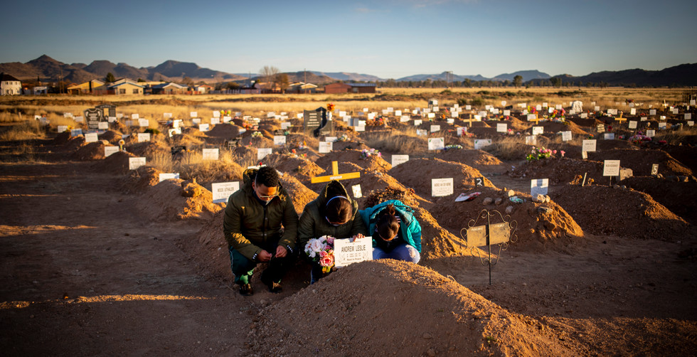 Widower Colette Leslie (46) and her two children, Curtley (L) and Adreulishe (R) pray at the graveside of their late father Captain Adrrew Leslie, Middleburg, South Africa, 14 June 2020. Captain Leslie died from the Covid-19 Corona virus a month earlier and was the first victim of the virus in the town. Be was acting station commander of the local police station. In the barren expanses of the Karoo (Great dry land) in the Eastern Cape province of South Africa, a perfect storm of circumstances has had a major and devastating effect on the local people. Three months of Covid-19 coronavirus lockdown, a harsh seven-year drought, and ongoing impact of the general economic slowdown over the past years along with an ill-prepared local and provincial government have left the vast majority of the local people under financial, physical and spiritual pressure.
