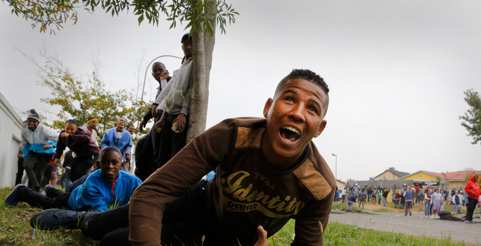 Protestors shelters behind a tree as they are fired at by police during a violent protest in Eldorado Park, Johannesburg, South Africa, 08 May 2017. Reports state that the local community took to the streets blocking major roads including the N1 and N12 as they protested over a lack of housing and land for their community. Continued protests over a lack of housing and service delivery are a weekly occurrence as many poorer communities stand up against the ANC (African National Congress) and President Jacob Zuma claiming a lack of service delivery since the end of Apartheid.