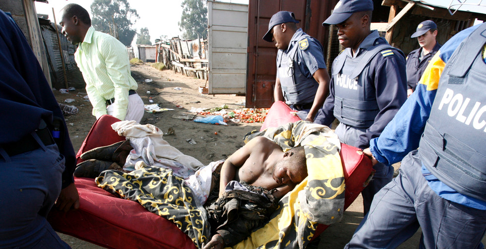 Police officers rescue a seriously injured man who had been attacked, beaten and burned during ongoing xenophobia attacks in Ramaphosa squatter camp east of Johannesburg, South Africa, 19 May 2008. An estimated 20 people have died with hundreds injured and thousands homeless after a week of violence by South Africans against any foreign Africans living in the city.