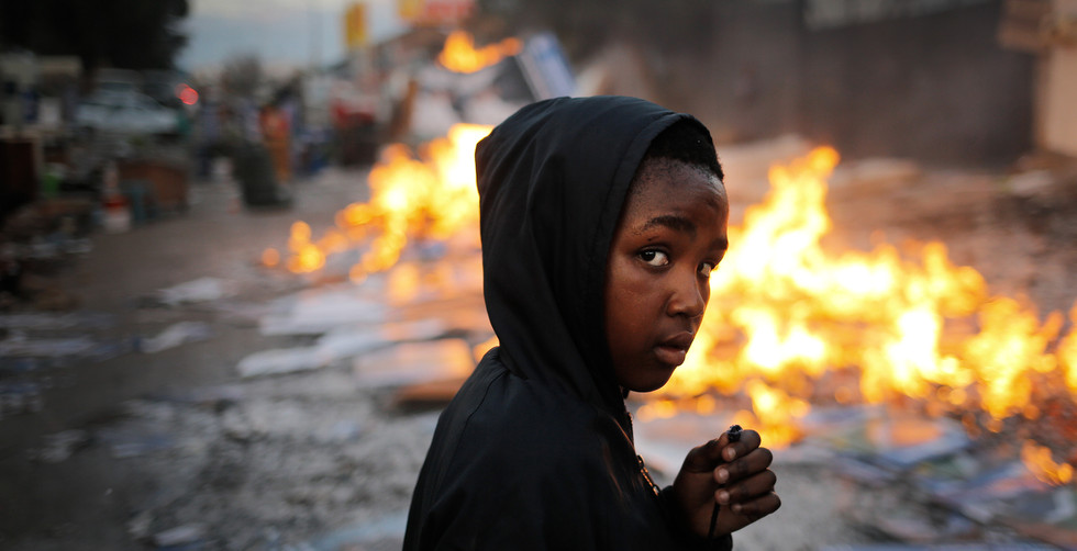 A young boy walks past a burning fire used to keep evicted families warm overnight after police and private security evicted families from a commercial property in Johannesburg, South Africa, 05 June 2014.