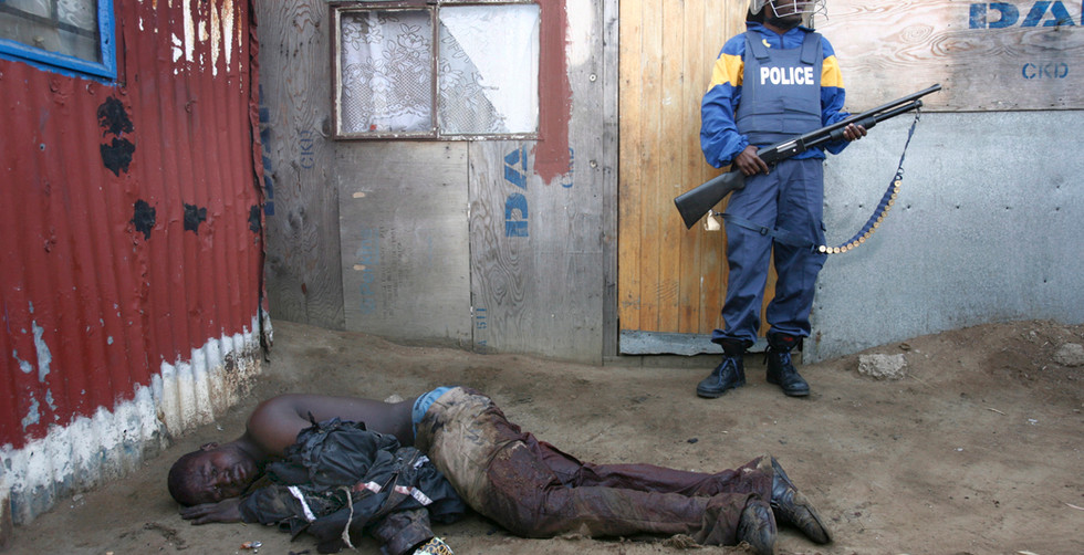 Police officers wait to rescue a seriously injured man who had been attacked, beaten and burned during ongoing xenophobia attacks in Ramaphosa squatter camp east of Johannesburg, South Africa, 19 May 2008. An estimated 20 people have died with hundreds injured and thousands homeless after a week of violence by South Africans against any foreign Africans living in the city.
