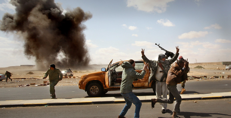 Rebel fighters run for cover as a bomb explodes near their position during another air raid by the Libyan Air force, Ras Lanuf, Libya, 2011.