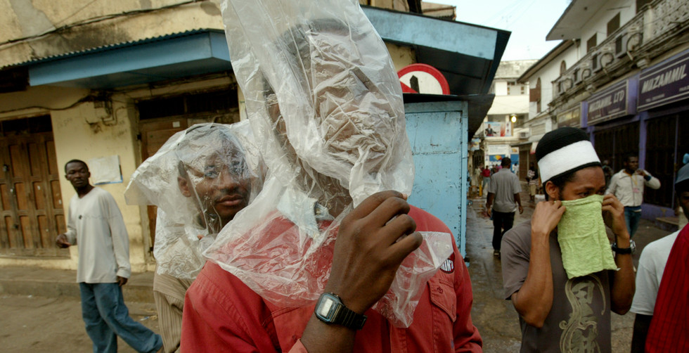 Civic United Front (CUF) supporters put plastic bags over their faces to counter the effects of teargas during post election violence in the streets of Stone Town Zanzibar Monday, 31 October 2005. Police arrested and beat scores of CUF supporters as running battles down the narrow allies of the ancient tourists town.