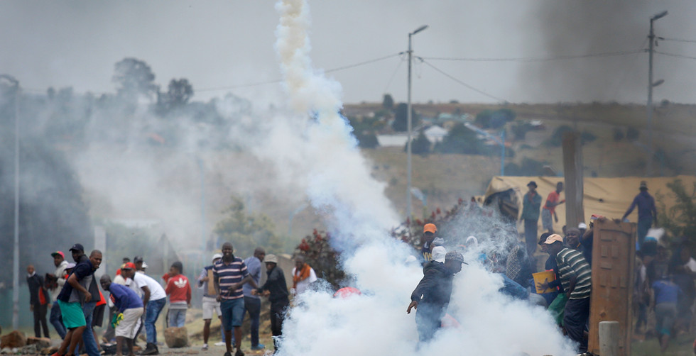 8 Protesters run from a police tear gas canister during fierce running battles after protesters took to the streets, Johannesburg, South Africa, 22 January 2018. Reports state protesters were angered by an attack on a local South African woman allegedly by Nigerians, an incident that sparked xenophobic protests in the streets of the West Rand area of the city.