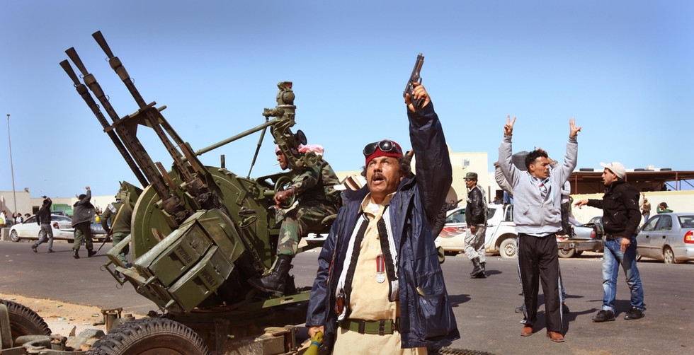 An elderly rebel wearing Second World War medals given to him by his father shoots his pistol into the air while anti-aircraft batteries fire at another Libyan Airforce jet flying over their position in Ras Lanuf, Libya.