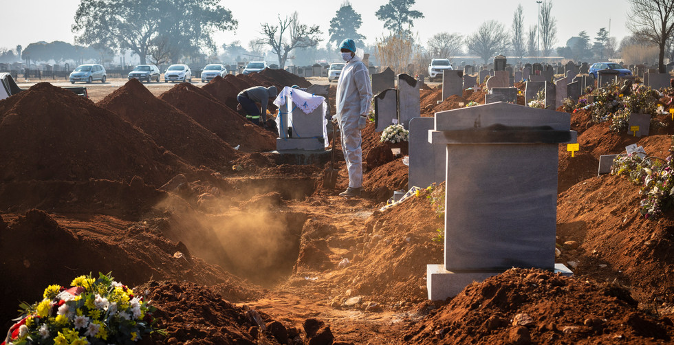 A family member wearing full PPE suite looks on after the funeral of a beloved elderly family member who died as a result of the elderly Covid-19 Corona virus at a graveyard on the 119 day of lockdown due to the Covid-19 Coronavirus, Johannesburg, South Africa, 24 July 2020. The un-named elderly lady was 84 years old and died at a state Hospital. South Africa has just reached the 450 000 infection mark from the pandemic accounting for almost two thirds of all cases registered to date in Africa and the fifth country with the highest number of infections worldwide.
