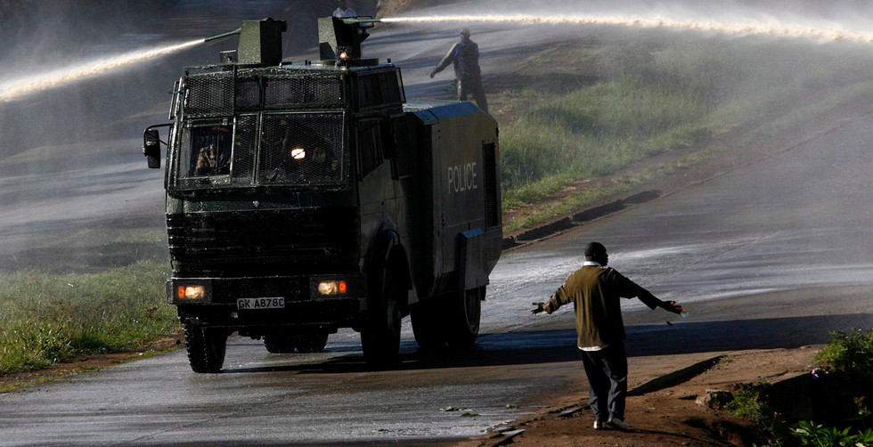 A lone Orange Democratic Movement supporter stands in front of a police tear gas truck in the streets of Nairobi, Kenya, 03 January 2008. Post election violence in the East African country has left hundreds of people dead with growing fears of further inter-tribal violence a possibility.