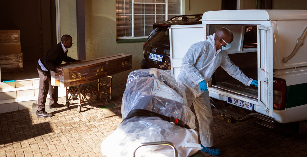 """Undertaker David Molofo sterilizes his vehicle after collecting a suspected Covid-19 Corona virus victim from a private house at the Avbob undertakers Germiston branch on the 116 day of lockdown due to the Covid-19 Coronavirus, Johannesburg, South Africa, 21 July 2020. Because of the widespread effects of the virus AVBOB now teats every case as a possible infection. When a call comes in, protective suits, face masks, face shields are prepared. The body must be removed, prepared for safe transport, legal documentation closed, and the funeral arranged within three days. The mortal remains must be sealed in three plastic bags: the first two are transparent so that they allow the identification of the deceased only by opening the third. Ironically AVBOB was born 102 years ago in response to the previous pandemic: the """"Spanish Flu"""" of 1918, which affected a third of humanity and killed between 50 and 100 million people. The soldiers who fought in World War I (1914-1918) inadvertently brought this virus to South Africa on their return from Europe."""