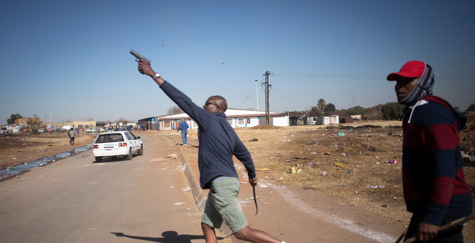 A taxi driver shoots his 9mm pistol into the air to chase nearby looters away from a mall after looting continued in the area, Johannesburg, South Africa, 14 July 2021.  Local taxi bosses and drivers have started to enforce their own law after police forces could not stop the ongoing looting of the mall in the East of Johannesburg
