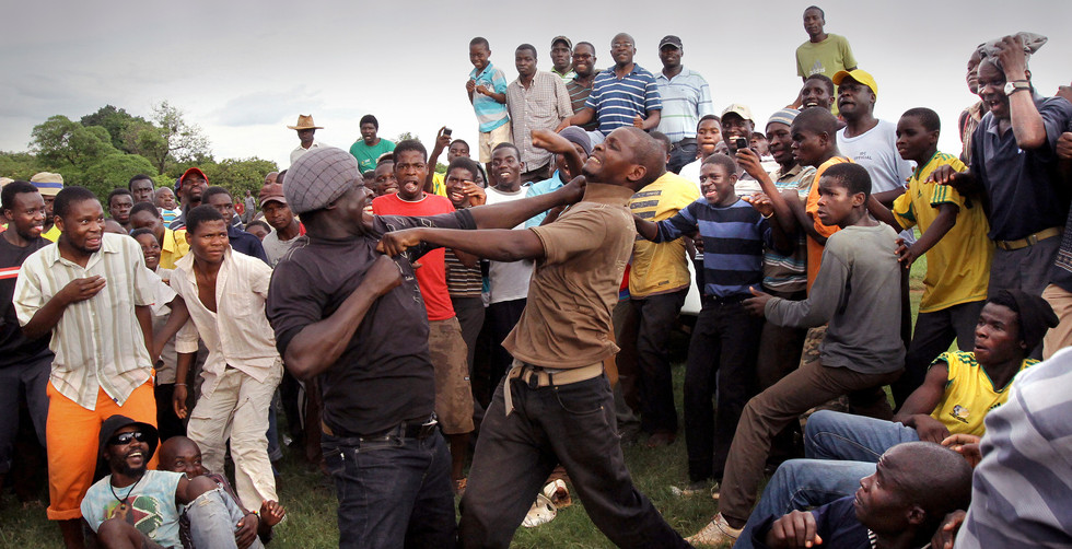 Two fighters exchange blows as they push into the crowd of fellow Venda men during the annual bare knuckle boxing match in the rural village of Tshisebi, Venda, South Africa, 16 December 2010.