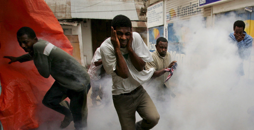 Opposition CUF supporters run as a tear gas canister explodes at their feet during running battles in the streets of Stone Town, Zanzibar, 31 October 2005. The supporters of the largely Muslim opposition battled with police in the run-up to the 2005 election.