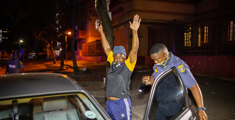 A man holds his hands in the air as a policeman checks his vehicle during SAPS (South African Police Force) operations to enforce the level 3 national lockdown in Hillbrow, Johannesburg, South Africa, 31 December 2020. The level 3 lockdown was implemented due to second wave of infections sweeping across the country many of which are  cases of a new variant of the Corivd-19 Corona virus 501.v2, a mutated SARS-CoV-2 variant which holds a higher transmission rate. South Africa is the first African nation to pass one million infections.
