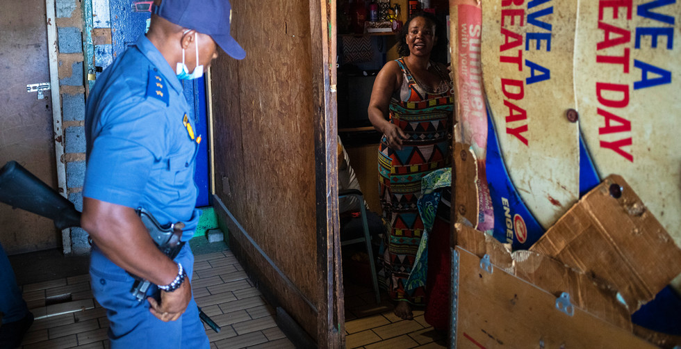 A member of the South African Police Services (SAPS) talks to a women inside her house during a joint SAPS and South African National Defense Force (SANDF) patrol on day 31 of the national lockdown as a result of the ongoing coronavirus COVID-19 pandemic in Johannesburg, South Africa, 26 April 2020.  The patrol was in the high density areas of Hillbrow and Yoeville where civilians are still breaking the strict lockdown rules. Those that where breaking the rules where arrested. South Africa's Stage 5 lockdown is due to end 30 April 2020 when stage 4 will be implemented.