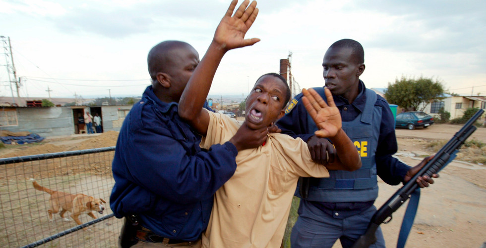 A man is arrested by police after shooting at their patrol during running battles with residents in the Diepsloot slum of Johannesburg, South Africa, 5 July 2004. Riots erupted in the slum over the lack of services and housing for shack dwellers.