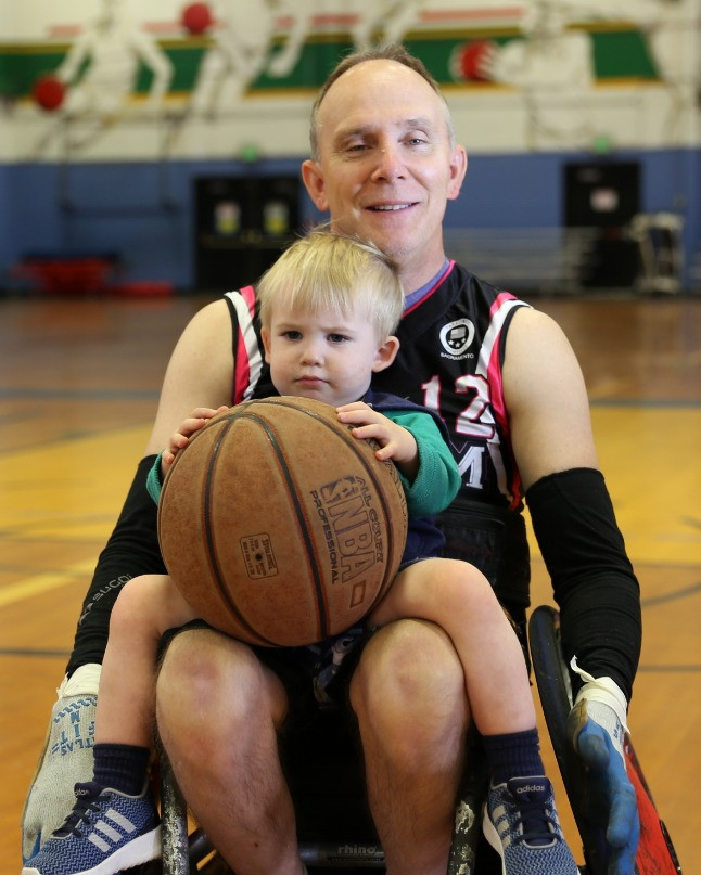 Image: Ed sitting in a sports wheelchair with his son inside of a gym.