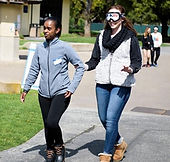 Two people outside walking. One person guiding the other person who's wearing a blindfold.