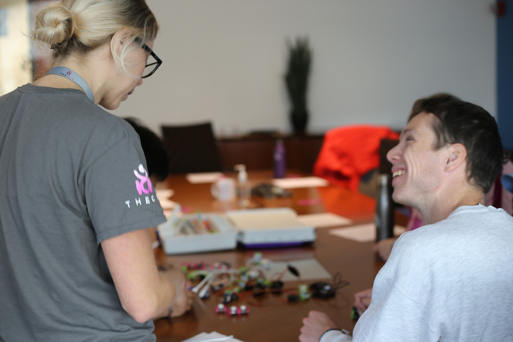 Reid (on the right) looking up at Jenni (on the left) as she is teaching him self-advocacy.