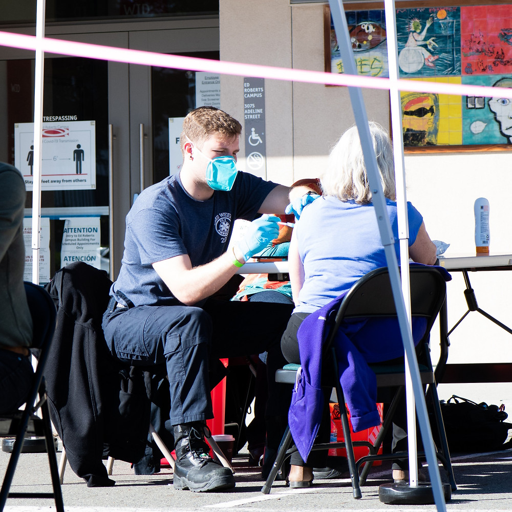 FEMA rep gives an older person a COVID-19 vaccine outside.