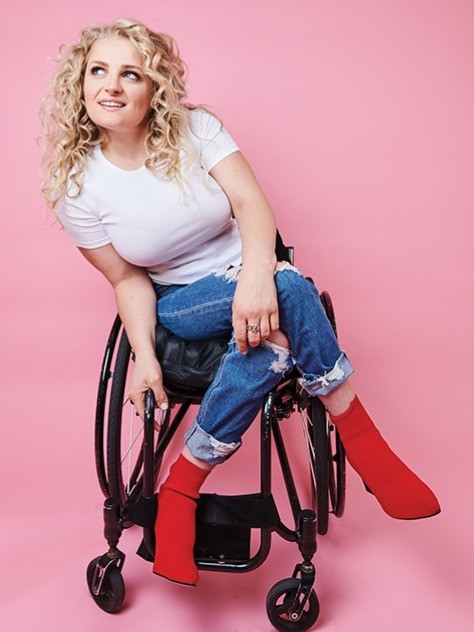 Ali Stroker sits in her manual wheelchair posing for the camera wearing a white shirt, long blue jeans, and red boots.