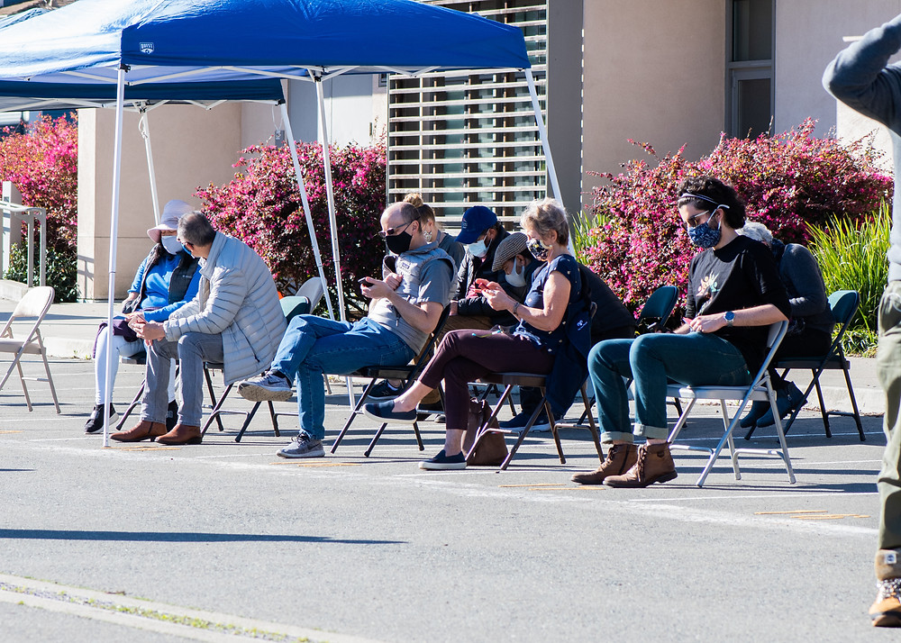 People sitting outside waiting after they got vaccinated.