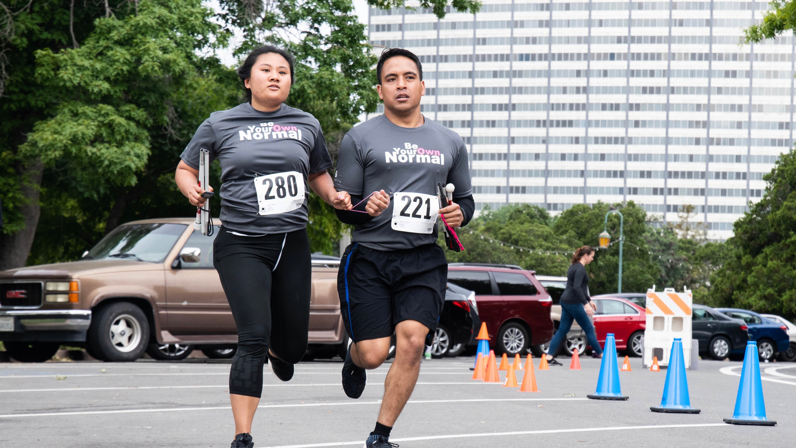 Two people with low vision running together