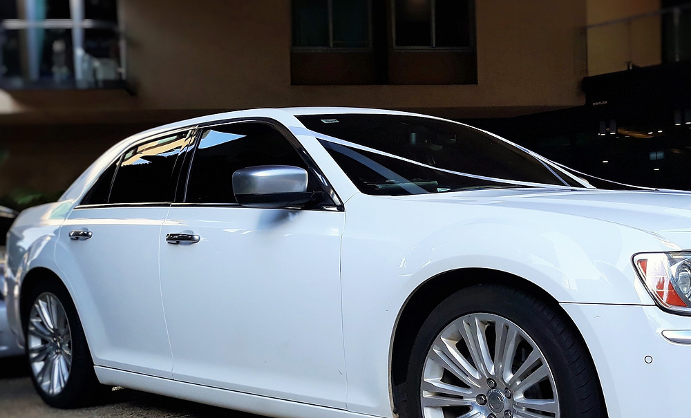 Our Luxury Chrysler 300C dressed in White Wedding Ribbon waits ready for Bride
