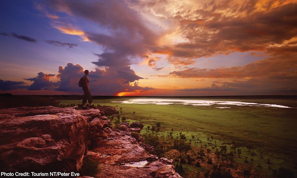 Lady standing on rocks at sunset, Kakadu National Park, Northern Territory Australia