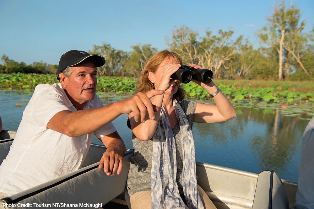 Lady and man in cruise wetland in boat at Kakadu National Park, Northern Territory Australia