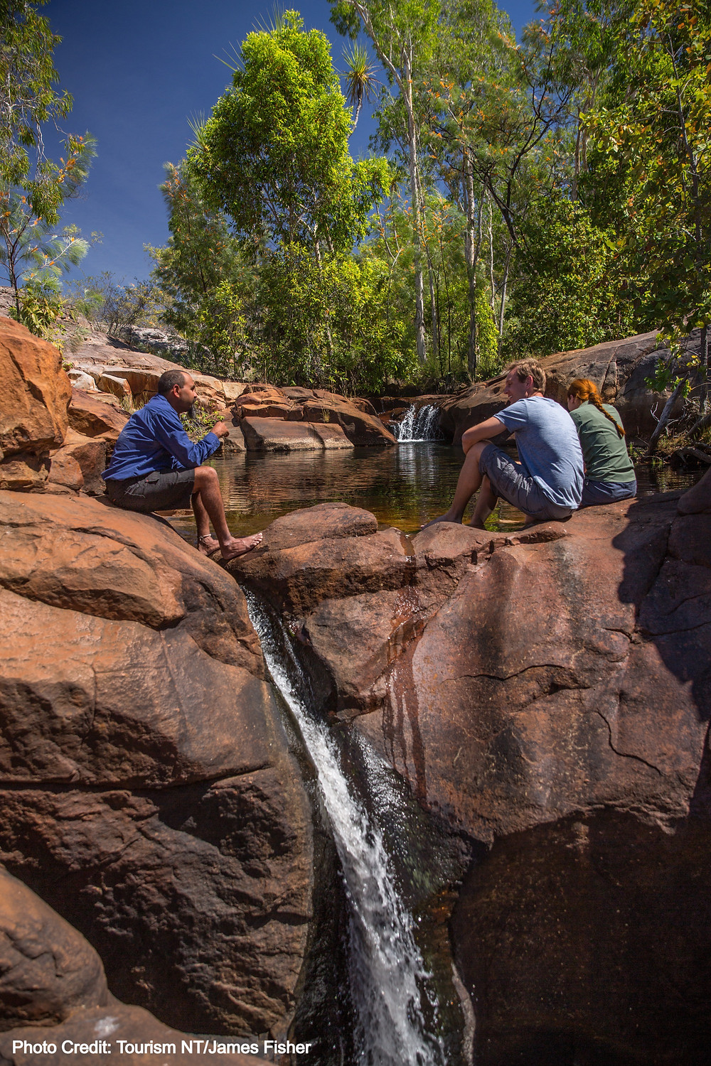 Couple with tour guide sitting beside rock pool at Kakadu National Park, Northern Territory Australia