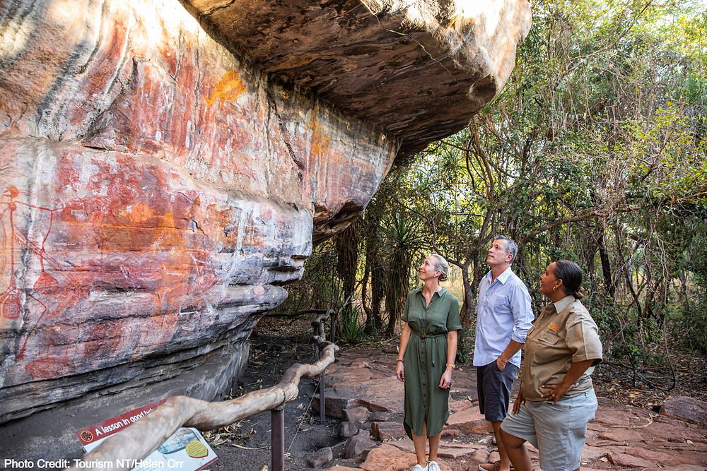 Couple with tour guide looking at rock art Kakadu National Park, Northern Territory Australia
