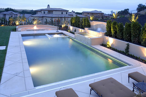 A pool with a waterfall in a luxury back