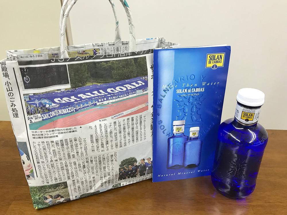 ひものんがもらってきた新聞バッグと高そうな水