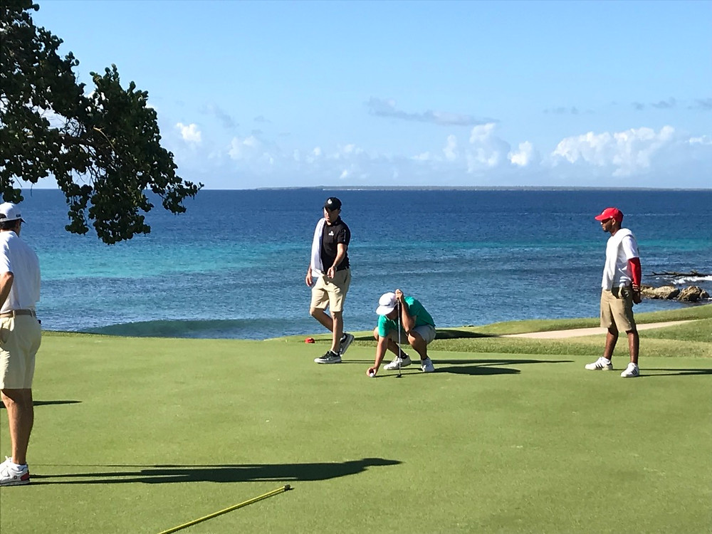Competitor lining up a putt on the green at Casa de Campo golf resort for the Latin America Amateur golf championship.  It is played on a Pete Dye course in the Dominican Republic.