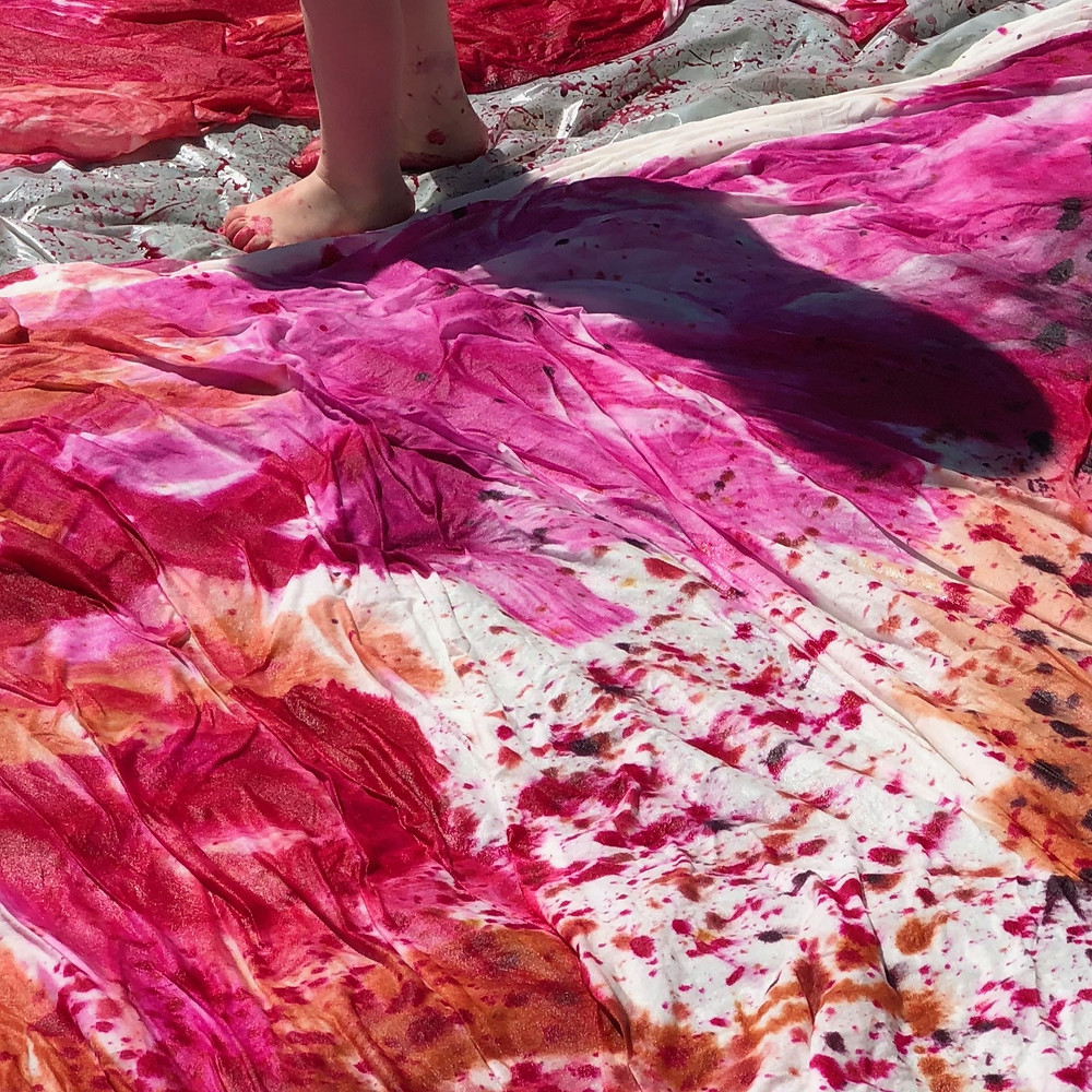 Little feet on plastic covered in fabric dye next to dye painted duvet covers.