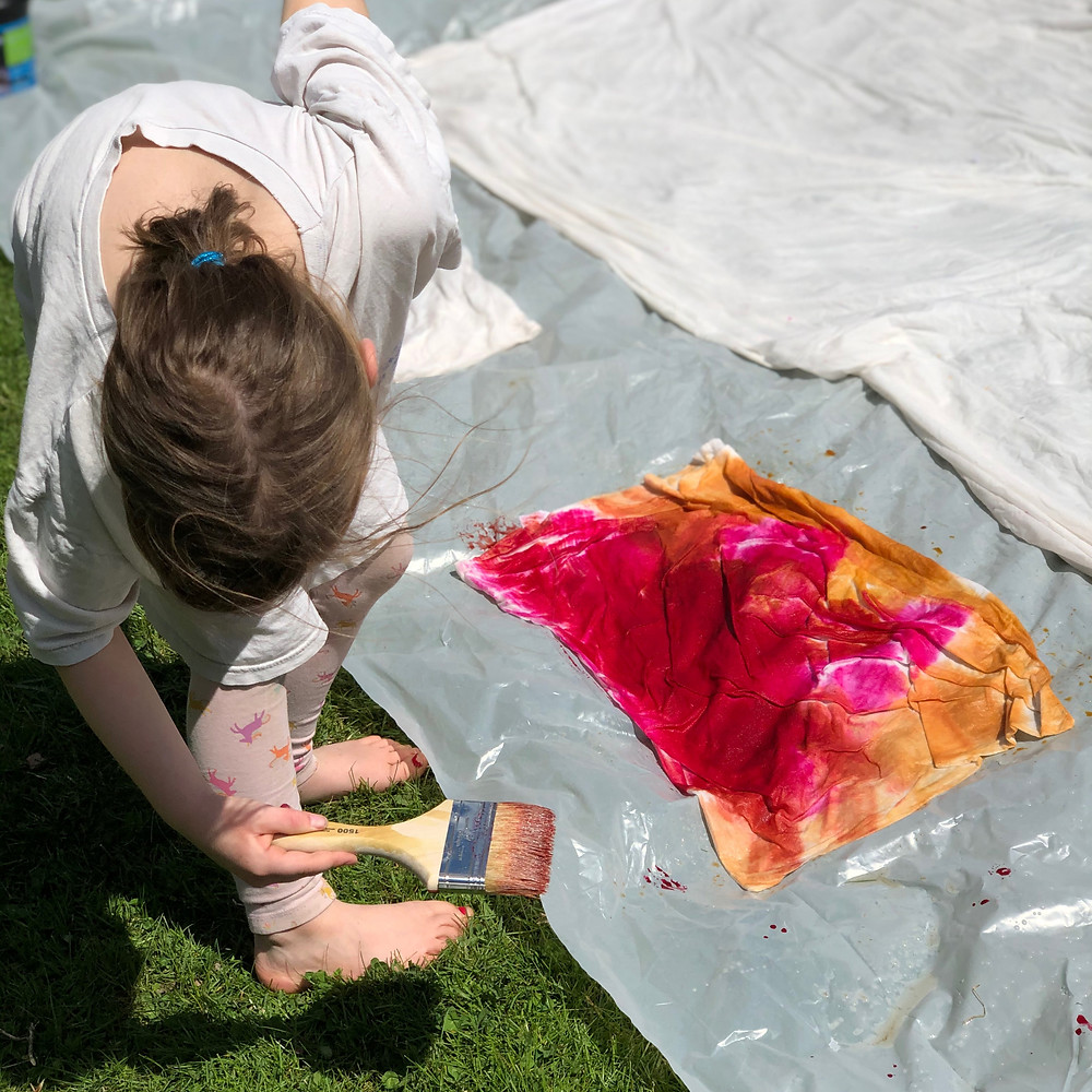 Young girl painting pillow case with pink and orange Dharma Trading Company Fiber Reactive Dye outside on plastic.