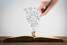person-drawing-symbols-coming-out-of-a-light-bulb-on-top-of-a-book.jpg