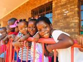 La joie de trois petites filles devant leur salle de classe.