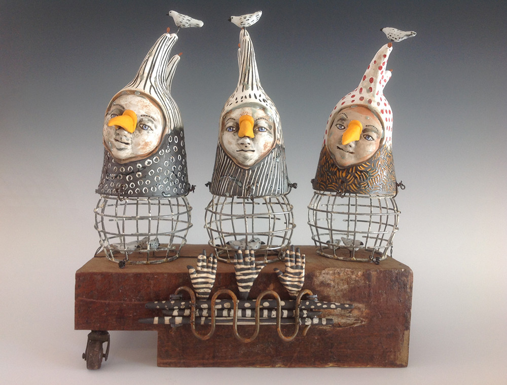 Three ceramic and wire figures perched on a wooden form.