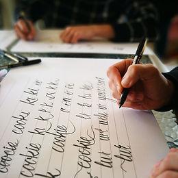 בחורה כותבת קליגרפיה בעטי מכחול באחת הסד
