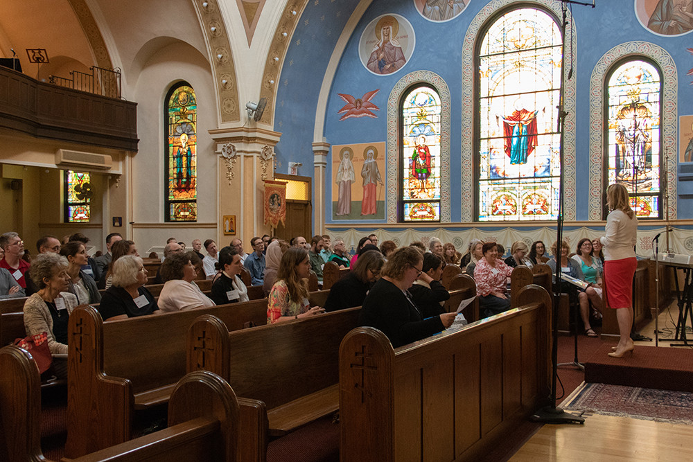 Juliana Woodill of Alexandria, Virginia, leading a choral rehearsal for the divine liturgy celebrated during the Symposium.