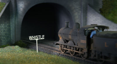 Locomotive entering tunnel with whistle sign.
